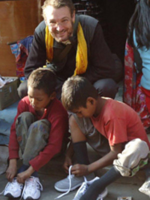 A volunteer helps Nepalese children tie their shoelaces.